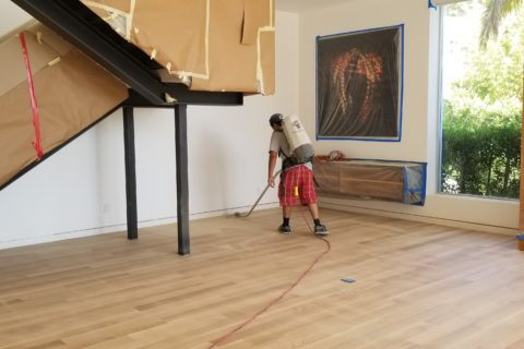 workman giving final touches to flooring in a newly designed or remodeled home