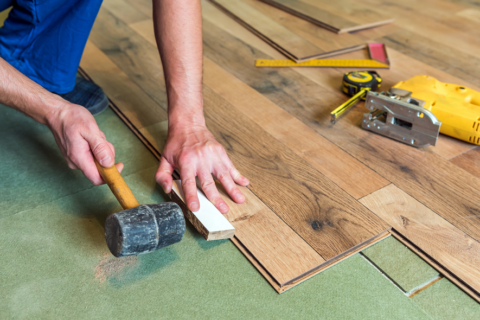 workman installing wood floors with his measuring tools and hammer